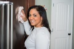 Hispanic Mom Cleaning. Happy hispanic mom cleaning her new refrigerator stock photo