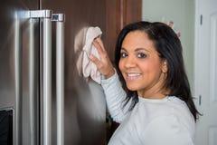 Hispanic Mom Cleaning. Happy hispanic mom cleaning her new refrigerator royalty free stock photos