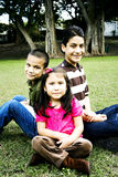 Happy hispanic siblings together in front of tree Stock Photography