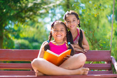 Happy hispanic sisters in summer park