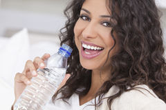 Happy Hispanic Woman Drinking Bottle of Water Stock Photo