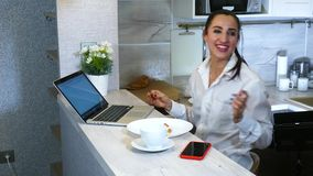 Happy Hispanic Woman Finish With Laptop Computer At Kitchen. Laughs and communicates with colleagues. stock video