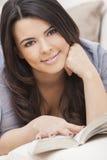 Happy Hispanic Woman Reading Paperback Book Stock Image