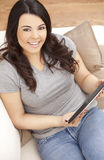 Happy Hispanic Woman Using Tablet Computer At Home stock photo