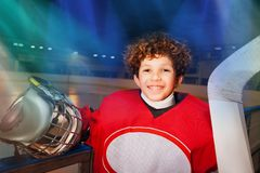 Happy hockey player standing next to the boards. Close-up portrait of young hockey player in red uniform, standing next to the boards of ice rink, smiling and stock images