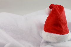 Happy holiday christmas with red christmas hat isolated. Close up of cute christmas hat in studio on a snowy soft white blanket Royalty Free Stock Images