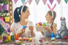 Family preparing for Easter. Happy holiday! A mother and her daughter are painting eggs. Family preparing for Easter. Cute little child girl is wearing bunny royalty free stock image