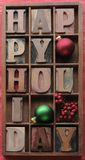 Happy holiday with ornaments, berries. Happy holiday in old wood letters in a type case with ornaments and berries stock photography