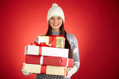 Happy holiday. Portrait of happy girl in winterwear holding stack of giftboxes over red background stock photography