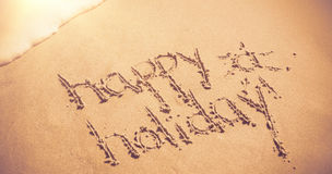 Happy holiday written on sand. At beach Stock Photo