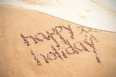 Happy holiday written text on sand Stock Photos