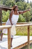 Happy holiday. Young dark-skinned overweight woman with sunhat leans over a wooden railing stock photo