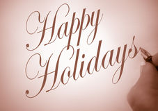 Happy Holidays. Person writing Happy Holidays in calligraphy script with sepia tone Stock Photo