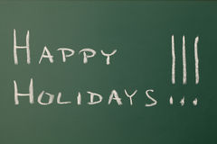Happy holidays. Green chalkboard with a text: Happy holidays Stock Images
