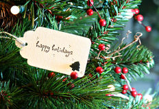 Happy Holidays. Card in a Christmas tree Royalty Free Stock Photography