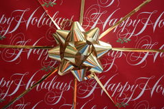 Happy Holidays. Wrapping paper with gold ribbon and bow royalty free stock photos