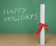 Happy holidays. Written on a chalkboard with a diploma on forefround Royalty Free Stock Photography
