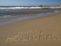 Happy holidays. Written on the sand beside the ocean Royalty Free Stock Images