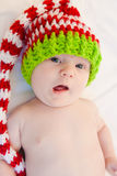Happy Holidays!. Baby wearing red white and green striped knit hat Stock Photos