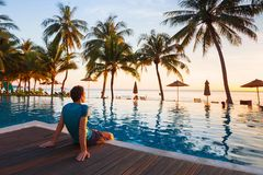 Man sitting near swimming pool and relaxing in luxury hotel stock images