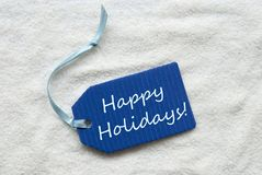 Happy Holidays On Blue Label Sand Background Stock Images
