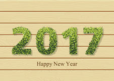 Happy holidays card with leaves on text 2017. And greeting text. 2017 new year color card on the wood texture. Vector illustration Stock Images