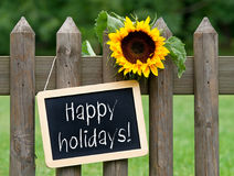 Happy holidays - chalkboard with sunflower. In the garden royalty free stock image
