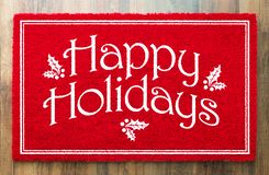 Happy Holidays Christmas Red Welcome Mat On Wood Floor Background.  stock photo