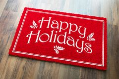 Happy Holidays Christmas Red Welcome Mat On Wood Floor Background.  stock images