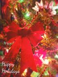 Holly Holidays. Happy Holidays, Christmas themed background: poinsettias, garland, lights, bells, ornaments, bow featured Royalty Free Stock Photo