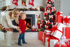 Happy holidays! Cute little child found many gifts under the Christmas tree. Royalty Free Stock Photography