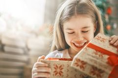 Child opening gift. Happy holidays! Cute little child opening gift at Christmas Stock Photos