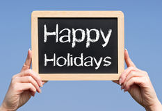 Happy Holidays - female hands holding chalkboard with text. On blue sky background royalty free stock images