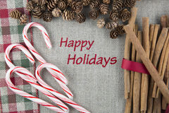 Happy Holidays Festive Card. Linen fabric printed with Happy Holidays surrounded by cinnamon sticks, candy canes and pine cones Royalty Free Stock Photography