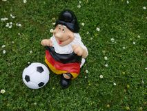 Hello Summer ! A funny garden gnome with a flag, a football and a bottle of beer sits happily on a green meadow. Happy holidays ! A funny garden gnome sits on a stock image