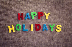 Happy Holidays giftcard made by multicolor letters on the contrast flax textile Stock Images