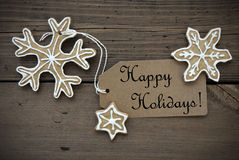 Happy Holidays with Ginger Breads. Happy Holidays Tag with some Ginger Bread Cookies with white Decoration on Wood Stock Images