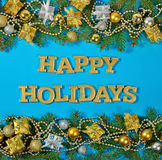 Happy holidays golden text and spruce branch and Christmas decor. Ations on a blue background Royalty Free Stock Photography