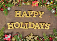 Happy holidays golden text and spruce branch and Christmas decor Stock Photography