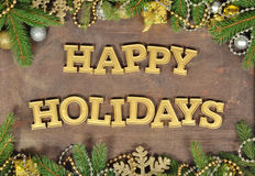 Happy holidays golden text and spruce branch and Christmas decor. Ations on a wooden background Royalty Free Stock Photos