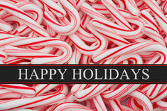 Happy Holidays Greeting. Candy Cane Background and text Happy Holidays Royalty Free Stock Photo