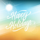 Happy Holidays greeting card. Hand drawn lettering text design on blurred summer beach background. Stock Photo