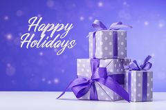 Happy holidays, greeting card in violet colors, background with snow. Boxes with gifts. royalty free stock photo
