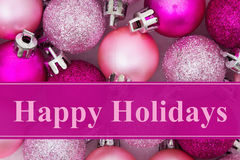 Happy Holidays greeting. Happy Holidays  greeting, Some pale and bright pink sparkle and matte Christmas ball ornaments with text Happy Holidays Royalty Free Stock Photos