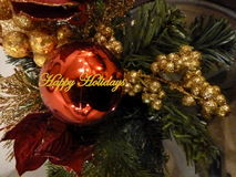 Happy Holidays greeting. Happy Holidays in yellow text graphics against ornaments on Christmas tree Stock Images