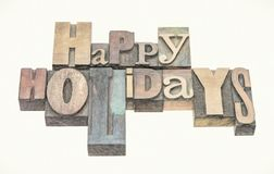 Happy Holidays greetings in wood type. Happy Holidays greeting card in mixed letterpress wood type printing blocks, digital painting effect applied to a stock photos