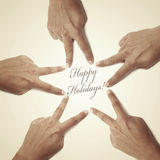 Happy holidays. Hands forming a christmas star and the sentence happy holidays written in it Stock Image