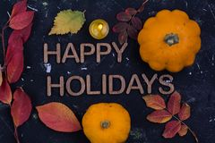 Happy holidays. Word with pumpkin and autumn leaves on black background royalty free stock image