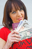 Happy holidays: just jetting off. An image of a happy girl about to leave for a holiday. She carries a passport, US Dollars and Pounds Stirling Royalty Free Stock Photos