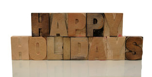 Happy holidays in letterpress wood type. The words 'happy holidays' in old wood type letters with a reflection Royalty Free Stock Images